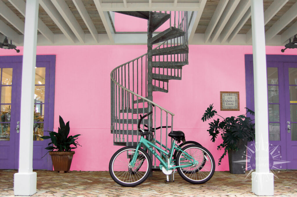 Turquoise bicycle against pink wall with purple doors