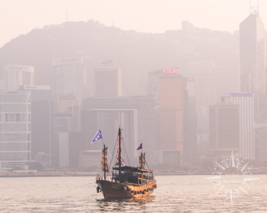 Boat in Hong Kong harbour with smog covering the skyline | air pollution