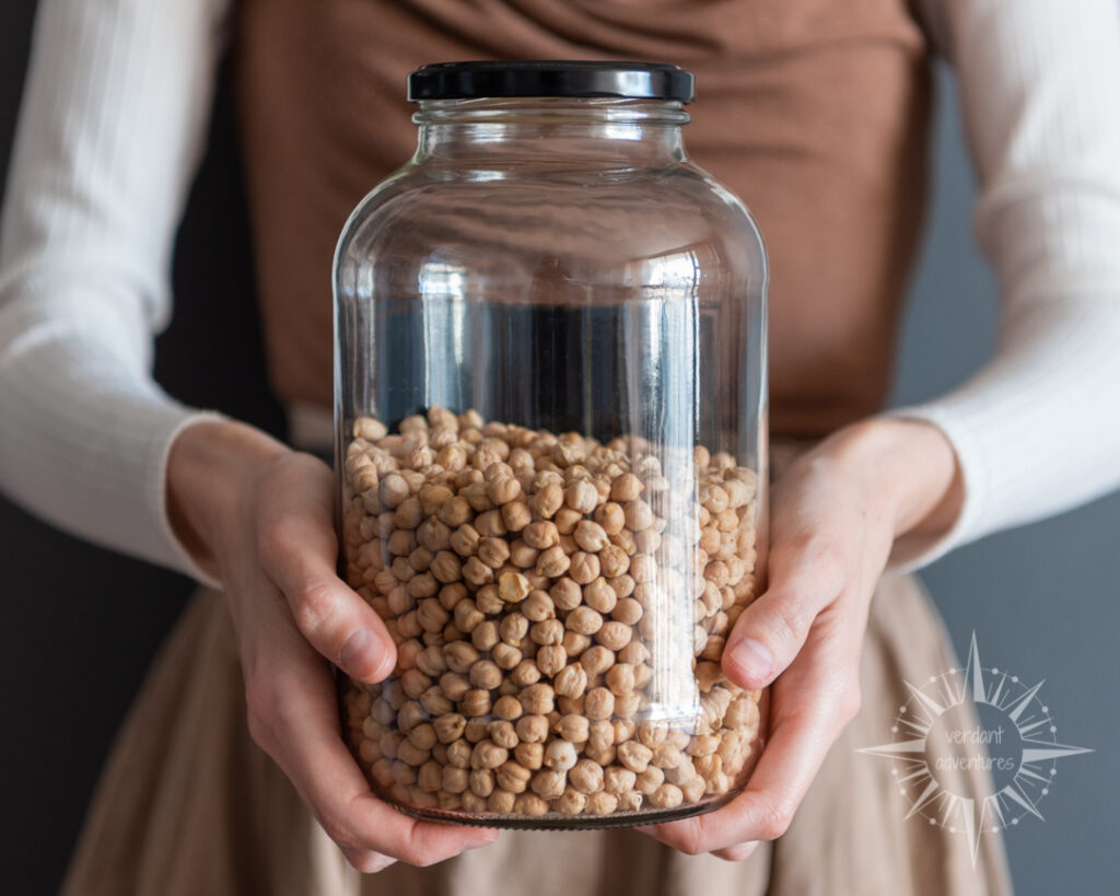 Hands holding a glass jar of chickpeas