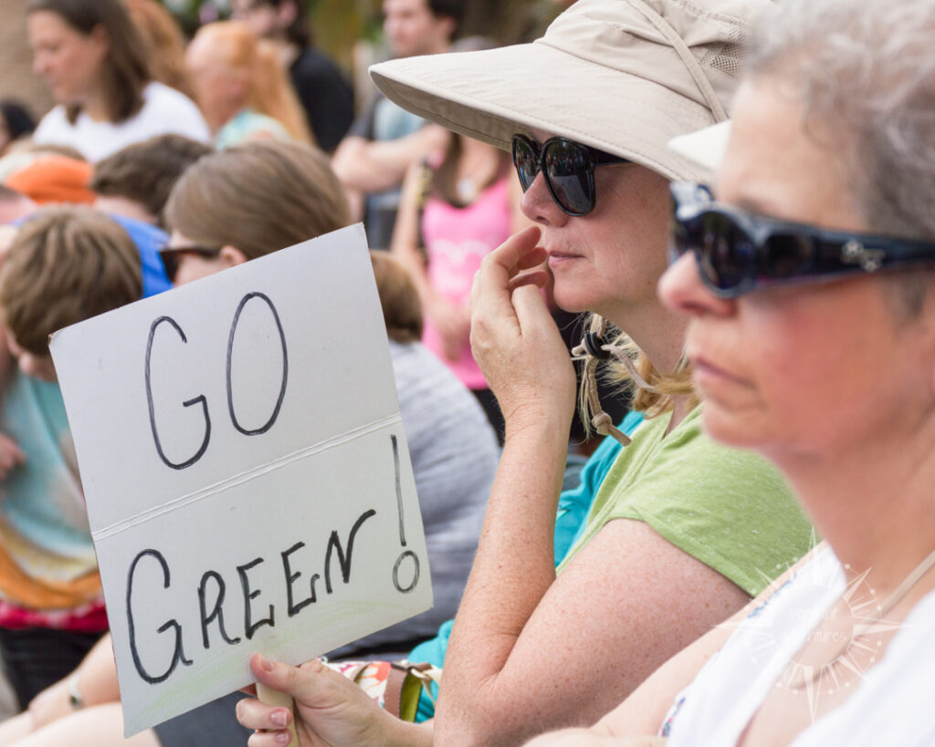 Women at the Orlando March for Science hold a sign that says Go Green to support environmental sustainability