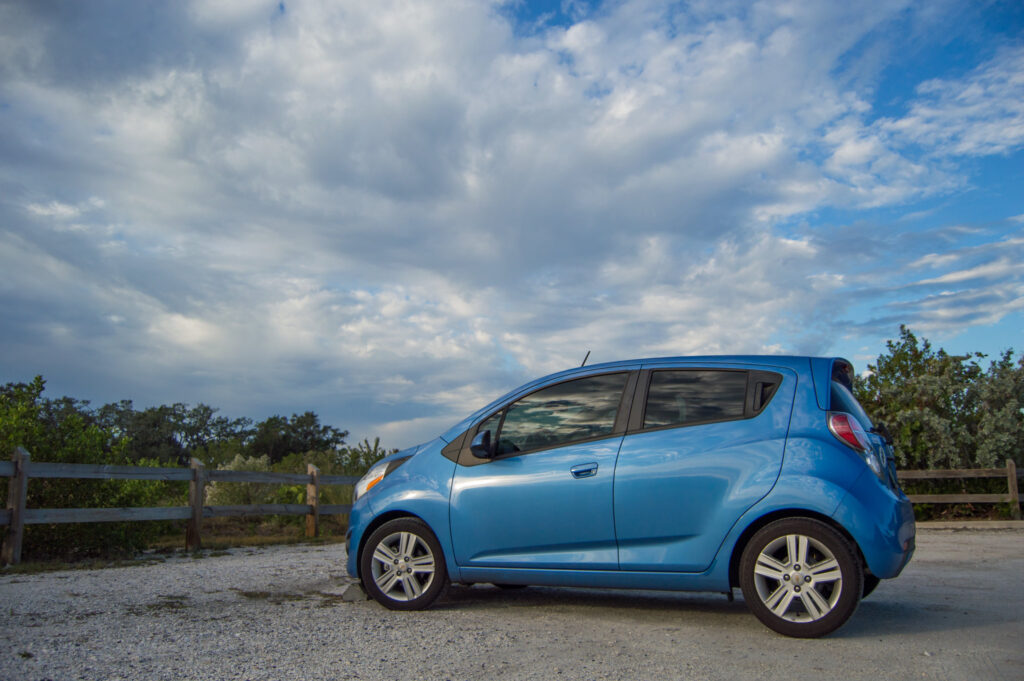 Little blue car against a bright blue sky with puffy white clouds | sustainability